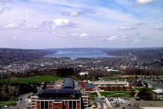 Cayuga Lake and Ithaca from the top of the Towers at Ithaca College, in Ithaca, NY in the Finger Lakes region. Cayuga Lake is the longest of the eleven Finger Lakes, 38 miles in length. You can only see about the southernmost 8 miles of the lake in this picture as it winds northward. Ithaca is also the home of Cornell University, which is on East Hill just out of view on the right side of this picture. Photo by Tony Ingraham, ithacafingerlakes.com.