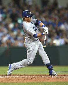 The Los Angeles Dodgers' Justin Turner singles into center in the top of the fifth inning during the Major League Baseball opening game between the Los Angeles Dodgers and Arizona Diamondbacks at the Sydney Cricket ground in Sydney, Saturday, March 22, 2014. (AP Photo/Rick Rycroft)