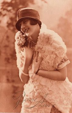 Click above to enlarge clip art Here's a great vintage sepia toned postcard that features a pretty Flapper lady! This card is labeled with a greeting of Bonne Annee. The woman pictured is wearing a wonderful cloche hat, a pearl necklace and a white fur stole.