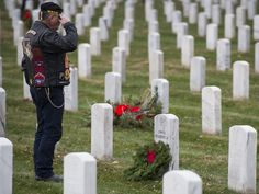 A Vietnam Veteran salutes after placing a wreath at a gravesite during the 2015 National Wreaths Across America event at Arlington National Cemetery in Arlington, Va.  Molly Riley, AFP/Getty Images