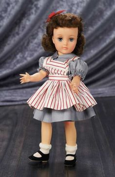 """Harriet Hubbard Ayers Doll with Original Costume,,1953  14"""" (36 cm.) Vinyl socket head,sleep eyes,lashes,brunette rooted curly hair,five piece body. She is wearing grey polished cotton dress w/attached panties,white striped pinafore,socks,shoes,Circa 1953.  Z"""