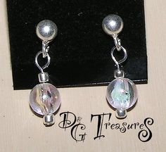 Earring 326 - $12 -- A pair of earrings with a 6mm Clear beads on each ear surrounded by a Sterling Silver seed beads, all held up by a Silver Plated Bronze headpin to a Sterling Silver 4mm ball post earring studs.