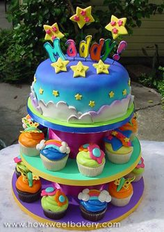 lisa frank cake on top of cupcake stand with matching cupcakes