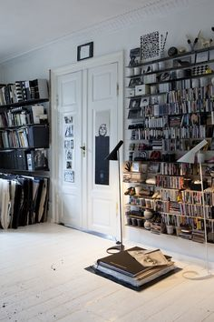 jam-packed book shelves + white-painted wood floors