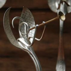 Wonderful fork art angel, handcrafted from vintage silverware by Ann Arbor Artist John Marchello. A fork forms the body of the angel, with the tines magically forming face, hands and halo. A spoon is split and etched to form the wings. Another spoon forms the base, and a brass tube becomes a trumpet. Each angel is unique, with variations in size and pattern. The finished height is about 8 to 9 inches.