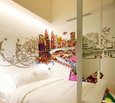 This here is a child's bedroom in Manhattan New York United States and the art design here really is the eye catching piece to the room because there is nothing else in the room except all white color which would be very dull itself but this amazing art design of a city with all different colors really brings it out.