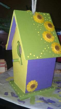 Simple birdhouse painted with bright colors. After painting was finished and then first layer of modge podge, flowers were added and then another thick layer of modge podge. A really fun craft :)