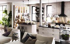 Una de nuestras cocinas favoritas, que da a un salón y tiene un estilo moderno y clásico con el color blanco como protagonista.