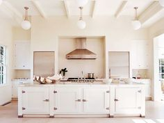 A sun-drenched white kitchen designed by Haynes-Roberts. Photo by Francois Halard via House & Garden.