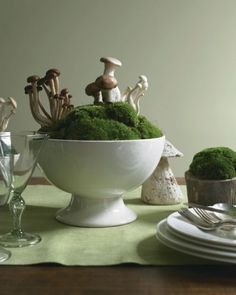 TOOTH PICK MUSHROOMS ON TO MOSS Bring spring foragers and a lush woodland carpet to the dinner table. Assorted mushrooms, including cremini, Trumpet Royale, honshimeji, and enoki, rise from a bed of cushion moss and lend an unexpected touch of whimsy. A wide ironstone tureen showcases the arrangement and helps anchor it among the table's place settings.