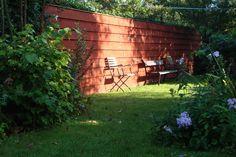Een sobere tuin oplichten met een gekleurde schutting