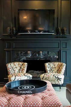 Black fireplace to camouflage the tv.- great looking paneled wall. tv set within w a marble mantle.
