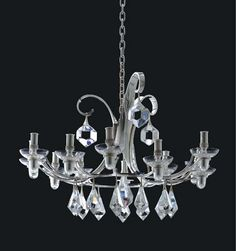 A SILVER TWELVE-LIGHT CHANDELIER DESIGNED BY HENNING KOPPEL  MARK OF GEORG JENSEN, COPENHAGEN, 1978  The twelve-arm chandelier with scroll triform standard, and hung with cut-glass drops, the chandelier convertible with detachable later fitted electrical sockets, and detachable glass sockets for candlelight, with silver suspension chain. Christie's.