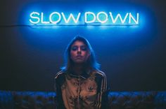 woman sitting on brown sofa under slow down neon signage photo – Free People Image on Unsplash