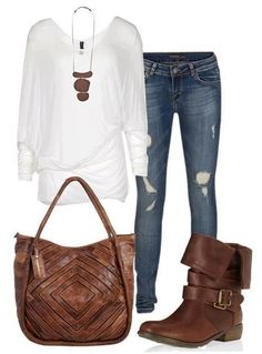White loose, ong sleeved shirt, distressed skinny jeans, brown handbag, brown boots with decorative strap.