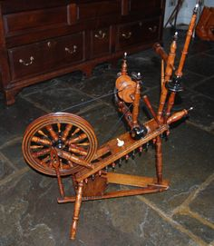 "Flax Spinning Wheel (c. 1780 Netherlands). A late 18th. century Oak and Inlaid Continental Flax Spinning Wheel, the 12"" diameter turned spindle wheel mounted on an oak base with sycamore and ebony geometric banding and embellished with Ivory Finials.  33.86 inches high  26.77 inches wide  15.75 inches deep"