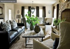 black leather couch. jute-seagrass rug-linen slip covered chairs.green plants