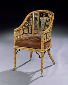 A rare early 19th century simulated bamboo and painted tub armchair in the chinoiserie taste, the pierced back with exotic compartments of bamboo decoration in simulated Chinese characters and designs within ebonised borders, with a simulated bamboo frame with sweeping arms and a caned seat with a brown suede cushion, raised on tapering legs terminating in brass castors.  English, circa 1810.