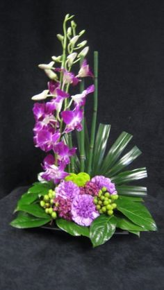 Purple Dendrobium Orchids, Purple carnations, Green Palm Leaf and Hypericum in a Black Dish $49.99