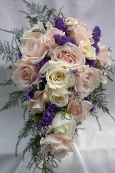 This bouquet has been recreated a few times from this picture.  It is a teardrop cascade of Champagne and white Sweetheart Roses with purple Statice Sinuata and Plumosa Fern
