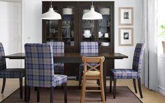 Mesa extensível e cadeiras em preto-castanho com capas xadrez e uma vitrina