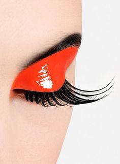 Glossy orange eyeshadow with dramatic black lashes