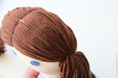 When you sew a doll together with all of this yarn, be sure to tuck the yarn out of the way while sewing the head together.  And remember how you left a 1/4 inch free at the top of each head piece?  Well, that's because when you sew the two head pieces together at the top, the yarn won't get in the way.  See the seam along the top of the head?  When you sew the head pieces together, the yarn should meet right up and hide the fabric below.