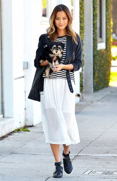 Jamie Chung wears a striped t-shirt, leather jacket, sheer midi skirt, and ankle boots