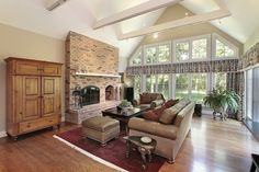 This living room with cathedral ceilings features a brick fireplace and plenty of natural light from full height windows.