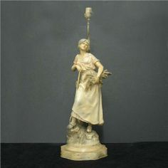 Painted spelter figural lamp; woman holdin