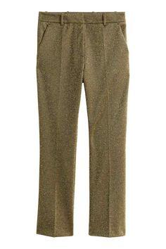 Calças em jersey brilhante: Calças de fato em jersey grosso com fios brilhantes. Têm fecho oculto de colchete na frente, bolsos laterais, bolsos traseiros falsos e pernas estreitas vincadas.