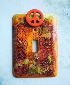This new-to-me artist has wonderful hand painted/adorned switch plates in her shop, as well as other things. Being a girl of the '60s, this caught my eye right away. Check it out! I think you will love them. -- Orange Peace light switch cover mixed media on by TMBakerDesigns