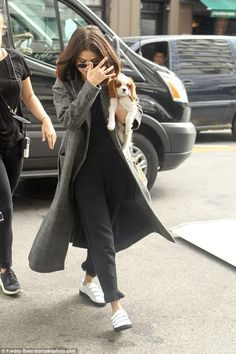 Cuddled up: Earlier, Selena kept her newly-adopted Cavalier King Charles Spaniel by her side as she made her way on set