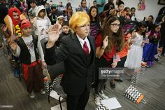 Dressed as Republican presidential candidate Donald Trump, 13-year-old Razvan Godja (C) and 26 other children wear Halloween costumes as they take the Oath of Allegiance during their naturalization ceremony at the U.S. Citizen and Immigration Services Washington Field Office October 30, 2015 in Washington, DC. Godja, who was born in Romania, and the other children became some of the United States' youngest and newest citizens on the day before heading out for the American tradition of…