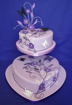 Two-tiered heart shaped wedding cake presented on an offset stand and decorated with piped black, purple and white swirls and leaves. Hand made purple sugar flowers add depth to the design which is enhanced with delicate butterflies.