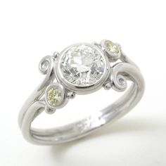 Caleb Meyer. European Cut and Fancy Diamond Ring. Forged and fabricated platinum ring set with a 1.06ct. European cut dimaond, clarity-VS2, color-J ., and a pair of fancy yellow round brilliant diamonds, 0.14ct. total weight.