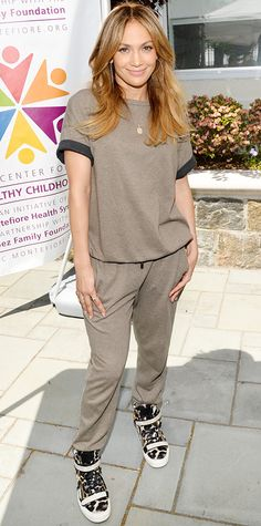Jennifer Lopez kicked back at the Montefiore Community Health Fair in sporty beige sweats by Brunello Cucinelli, elevating them with a delicate gold jewelry and extra-cool leopard print sneaks.