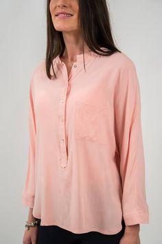 Tunică din material fin, vaporos, de culoare roz prăfuit. Este acccesorizată în zona pieptului cu un buzunar aplicat și nasturi dispuși vertical. Mâneci lungi, neaccesorizate. Terminație asimetrică, rotunjită.