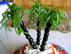Palm Trees made from black olives on a skewer, topped with julienned green pepper or green onions