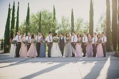 Beautiful winery wedding at Mount Palomar Winery in Temecula.  Blush and gray bridal party in front of the cypress trees planted at this Temecula vineyard wedding venue. #mountpalomarwinerywedding