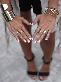 White polish + gold rings and bangles.