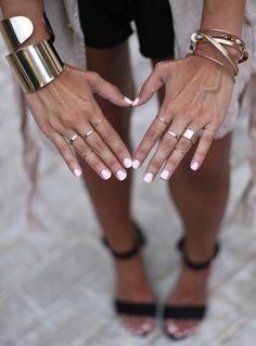 White polish + gold rings and bangles.