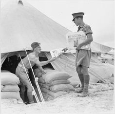 The morning paper being delivered at camp in the Western desert, 16 October 1941.