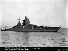 Good shot for clipper bow fans! Battleship Number 40, USS New Mexico, off the Puget Sound Navy Yard, Bremerton, Washington, following overhaul, 6 October 1943. A barge and motor launch are alongside her starboard quarter, with sailors coming on board from