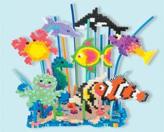 This bright underwater reef scene features lots of sea creatures including a clown fish, octopus, seahorse, crab, dolphin, and more. The scene is made dimensional with the use of Perler bead stems that attach to each creature and anchor into the reef base.