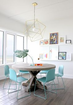 a light and bright dining room with a metal brass geometric hanging pendant light over a circular wood table and light blue plastic dining chairs