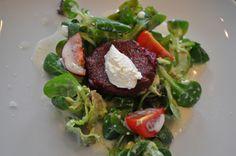 4. Gang des Weihnachtsmenüs.  Ein kleiner roter Beete-Bratling auf Feldsalat mit einem Senfdressig. Oben drauf ein kleiner Löffel Meerrettich-Creme.
