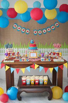 Ideia de painel simples, feito com cartolina e arrumado como varal! Ideia de bandeirolas na cores do tema da festa! Mesa da Galinha Pintadinha e sua turma