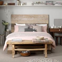 Coastal-inspired bedroom   Reclaimed timber planks make up this bed frame and headboard to provide a rough-and-ready coastal vibe. The look, decorated in shades of grey, off-whites, dusty pinks and browns, is completed with sisal flooring and nubbly rugs.   Via: Housetohome
