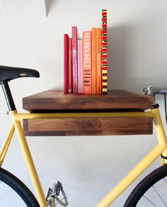 Wouldn't it be nice if you could put your bike on the shelf, like a book, and take it from it only when you need it? Well, this exact idea inspired Bike Shelf, created by the San-Francisco based designer Chris Brigham (aka Knife and Saw). The piece is made from walnut or ash and can be attached to the wall via a steel rod mount. The flat surface on top can serve as an actual book shelf or provide storage for bike accessories and other small items.